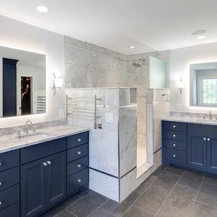 Modelo de cuarto de baño principal, clásico renovado, grande, con armarios con paneles lisos, puertas de armario azules, bañera exenta, ducha abierta, sanitario de dos piezas, baldosas y/o azulejos grises, baldosas y/o azulejos de porcelana, paredes grises, suelo de baldosas de porcelana, lavabo bajoencimera, encimera de granito, suelo gris, ducha abierta y encimeras grises