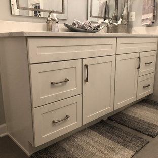 На фото: главная ванная комната среднего размера в стиле современная классика с фасадами в стиле шейкер, белыми фасадами, накладной ванной, угловым душем, раздельным унитазом, серой плиткой, мраморной плиткой, серыми стенами, врезной раковиной, столешницей из искусственного кварца, желтым полом, душем с раздвижными дверями, белой столешницей, унитазом, тумбой под две раковины и встроенной тумбой с