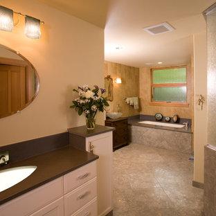 Modelo de cuarto de baño tradicional renovado con armarios con paneles con relieve, puertas de armario blancas, bañera encastrada, ducha empotrada, paredes beige, lavabo bajoencimera y encimera de esteatita