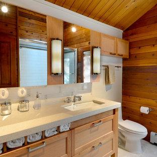 シアトルの広いラスティックスタイルのおしゃれなバスルーム (浴槽なし) (シェーカースタイル扉のキャビネット、淡色木目調キャビネット、白いタイル、アンダーカウンター洗面器、茶色い壁、アルコーブ型シャワー、一体型トイレ、サブウェイタイル、セラミックタイルの床、白い床、引戸のシャワー、ベージュのカウンター) の写真