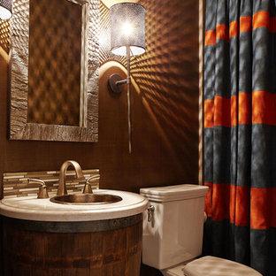 Cette photo montre une petit salle d'eau chic avec un lavabo posé, des portes de placard en bois brun, un plan de toilette en surface solide, une baignoire en alcôve, un combiné douche/baignoire, un WC séparé, un carrelage marron, des carreaux de céramique, un mur marron et un sol en carrelage de porcelaine.