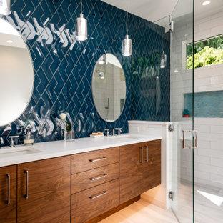 Стильный дизайн: главная ванная комната среднего размера в стиле модернизм с плоскими фасадами, коричневыми фасадами, душем без бортиков, раздельным унитазом, синей плиткой, керамогранитной плиткой, белыми стенами, полом из керамогранита, врезной раковиной, столешницей из искусственного кварца, серым полом, душем с распашными дверями, белой столешницей, нишей, тумбой под две раковины, встроенной тумбой и панелями на стенах - последний тренд