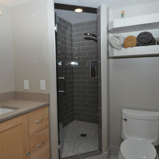Imagen de cuarto de baño con ducha, minimalista, pequeño, con armarios con paneles lisos, puertas de armario de madera clara, ducha esquinera, sanitario de dos piezas, baldosas y/o azulejos de vidrio laminado, paredes blancas, lavabo bajoencimera y encimera de cuarcita
