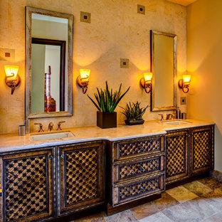 フェニックスの小さい地中海スタイルのおしゃれな浴室 (アンダーカウンター洗面器、ベージュのタイル、中間色木目調キャビネット、ラミネートカウンター、石タイル、ベージュの壁、アルコーブ型シャワー) の写真