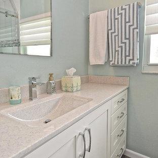 Modelo de cuarto de baño con ducha, costero, pequeño, con armarios con paneles empotrados, puertas de armario blancas, paredes azules, lavabo integrado, encimera de ónix, suelo gris, encimeras beige y suelo vinílico