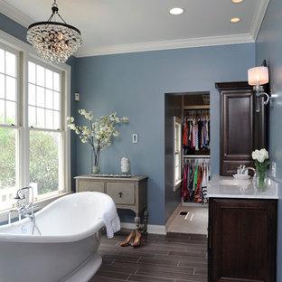 Свежая идея для дизайна: ванная комната в классическом стиле с отдельно стоящей ванной, фасадами с утопленной филенкой, темными деревянными фасадами и коричневым полом - отличное фото интерьера