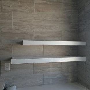 Immagine di una stanza da bagno padronale minimal di medie dimensioni con ante con riquadro incassato, ante in legno bruno, piastrelle grigie, piastrelle in gres porcellanato, pavimento in legno massello medio, lavabo sottopiano e top in quarzo composito