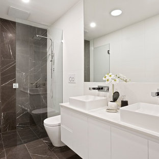 Contemporary bathroom in Melbourne with flat-panel cabinets, white cabinets, a curbless shower, gray tile, white walls, a vessel sink, grey floor, a hinged shower door and white benchtops.