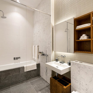 Design ideas for a contemporary bathroom in London with open cabinets, dark wood cabinets, an alcove bath, white tiles, white walls, a wall-mounted sink and grey floors.