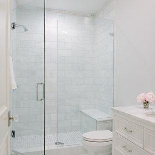 Klassisk inredning av ett vit vitt badrum, med möbel-liknande, vita skåp, en dusch i en alkov, en toalettstol med separat cisternkåpa, vit kakel, grå väggar, klinkergolv i porslin, ett undermonterad handfat, marmorbänkskiva, grått golv och dusch med gångjärnsdörr