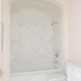 Foto de cuarto de baño clásico renovado con armarios tipo mueble, puertas de armario blancas, bañera empotrada, combinación de ducha y bañera, sanitario de dos piezas, baldosas y/o azulejos rosa, paredes azules, suelo de baldosas de porcelana, lavabo bajoencimera, encimera de mármol, suelo gris, ducha abierta y encimeras blancas