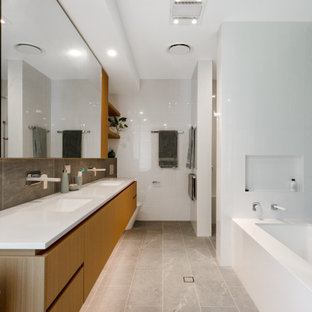Photo of a contemporary master bathroom in Brisbane with furniture-like cabinets, light wood cabinets, an undermount tub, an alcove shower, a wall-mount toilet, gray tile, porcelain tile, grey walls, porcelain floors, an undermount sink, engineered quartz benchtops, grey floor, an open shower, white benchtops, a shower seat, a double vanity and a floating vanity.