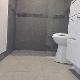 Imagen de cuarto de baño con ducha, tradicional renovado, de tamaño medio, con armarios con paneles lisos, puertas de armario blancas, ducha empotrada, sanitario de dos piezas, baldosas y/o azulejos grises, baldosas y/o azulejos de porcelana, paredes grises, suelo laminado y suelo gris