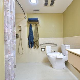 タンパの中くらいのトランジショナルスタイルのおしゃれなマスターバスルーム (バリアフリー、黄色い壁、淡色無垢フローリング、珪岩の洗面台、分離型トイレ、シャワーカーテン) の写真