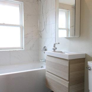 ポートランドの小さいモダンスタイルのおしゃれなバスルーム (浴槽なし) (フラットパネル扉のキャビネット、淡色木目調キャビネット、アルコーブ型浴槽、シャワー付き浴槽、分離型トイレ、白いタイル、大理石タイル、グレーの壁、ラミネートの床、一体型シンク、珪岩の洗面台、黒い床、オープンシャワー) の写真