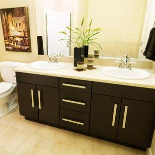 Idee per una piccola stanza da bagno padronale minimal con lavabo da incasso, ante lisce, ante in legno bruno, top in granito, vasca ad alcova, vasca/doccia, WC monopezzo, piastrelle nere, piastrelle in ceramica, pareti beige e pavimento con piastrelle in ceramica