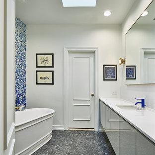 Diseño de cuarto de baño infantil, minimalista, de tamaño medio, con armarios con paneles lisos, puertas de armario grises, bañera exenta, sanitario de pared, baldosas y/o azulejos azules, baldosas y/o azulejos de vidrio laminado, paredes blancas, suelo de corcho, lavabo bajoencimera, encimera de cuarcita, ducha a ras de suelo, suelo blanco y ducha con puerta con bisagras