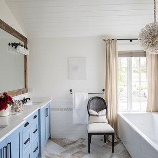 Пример оригинального дизайна: ванная комната в классическом стиле с фасадами в стиле шейкер, синими фасадами, отдельно стоящей ванной, белыми стенами, врезной раковиной, бежевым полом, белой столешницей, тумбой под две раковины, встроенной тумбой, потолком из вагонки и сводчатым потолком