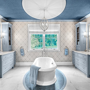This is an example of a large country master bathroom in Grand Rapids with raised-panel cabinets, blue cabinets, a freestanding tub, multi-coloured walls, marble floors, an undermount sink, quartzite benchtops, white floor, white benchtops, a double vanity, a built-in vanity, wallpaper and wallpaper.