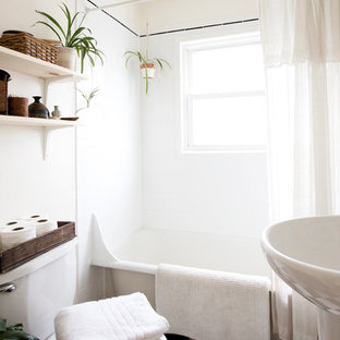 Inspiration for a small midcentury bathroom in Portland with a pedestal sink, a claw-foot tub, white walls and linoleum floors.