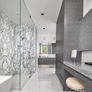 Modernes Badezimmer mit Beton-Waschbecken/Waschtisch, flächenbündigen Schrankfronten, grauen Schränken, freistehender Badewanne, bodengleicher Dusche, schwarz-weißen Fliesen, Steinplatten, weißer Wandfarbe, weißem Boden, Falttür-Duschabtrennung und grauer Waschtischplatte in Washington, D.C.