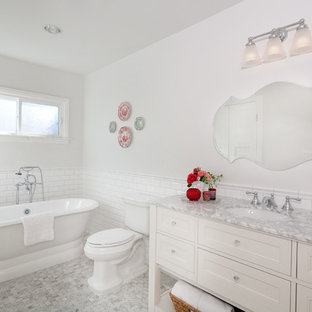 Example of a mid-sized classic 3/4 white tile and subway tile porcelain floor freestanding bathtub design in Denver with recessed-panel cabinets, white cabinets, a two-piece toilet, white walls, an undermount sink, marble countertops and gray countertops