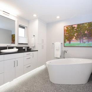 На фото: главная ванная комната среднего размера в современном стиле с плоскими фасадами, белыми фасадами, отдельно стоящей ванной, белыми стенами, полом из терраццо, настольной раковиной, серым полом, черной столешницей, тумбой под одну раковину и подвесной тумбой с