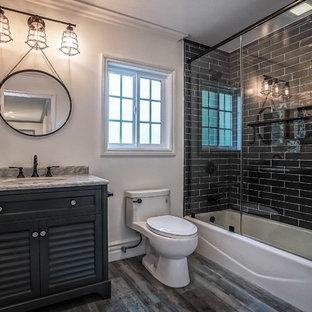 Свежая идея для дизайна: большая главная ванная комната в стиле ретро с фасадами с филенкой типа жалюзи, черными фасадами, ванной в нише, душем над ванной, унитазом-моноблоком, разноцветной плиткой, керамической плиткой, белыми стенами, полом из керамической плитки, врезной раковиной, столешницей из искусственного кварца, разноцветным полом и душем с распашными дверями - отличное фото интерьера