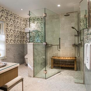 Cette image montre une grand salle d'eau traditionnelle avec une douche à l'italienne, un WC suspendu, un carrelage gris, un mur gris, un plan de toilette en verre, un placard avec porte à panneau encastré, des portes de placard en bois brun, des carreaux de porcelaine, un sol en carrelage de porcelaine, un lavabo encastré, une cabine de douche à porte battante et un sol gris.