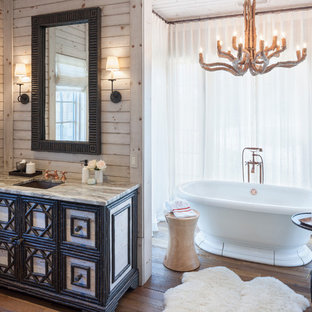 Example of a huge mountain style master medium tone wood floor freestanding bathtub design in Grand Rapids with furniture-like cabinets, an undermount sink and multicolored countertops