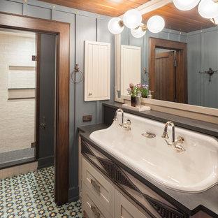 Imagen de cuarto de baño con ducha, rural, extra grande, con armarios tipo mueble, puertas de armario blancas, baldosas y/o azulejos blancos, paredes azules, lavabo de seno grande, suelo multicolor, ducha con puerta con bisagras y encimeras negras