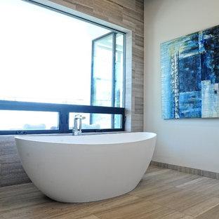 Modelo de cuarto de baño principal, actual, grande, con bañera exenta, baldosas y/o azulejos blancos, suelo de baldosas tipo guijarro, paredes blancas, suelo de baldosas de cerámica y suelo beige