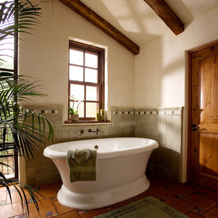 Large southwest master terra-cotta floor freestanding bathtub photo in Santa Barbara with beige walls