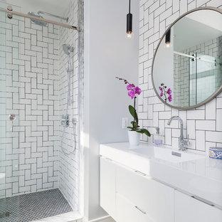 Kleines Modernes Badezimmer En Suite mit flächenbündigen Schrankfronten, weißen Schränken, weißen Fliesen, Metrofliesen, weißer Wandfarbe, Marmorboden, integriertem Waschbecken, Duschnische und Schiebetür-Duschabtrennung in Toronto