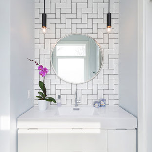 Small contemporary ensuite bathroom in Toronto with flat-panel cabinets, white cabinets, white tiles, metro tiles, white walls, marble flooring, an integrated sink and solid surface worktops.