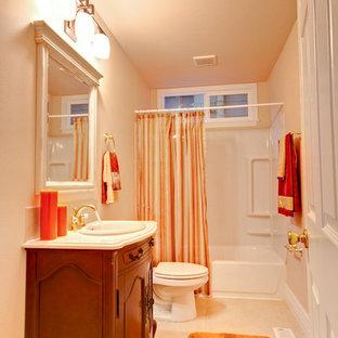 Modelo de cuarto de baño clásico, de tamaño medio, con armarios tipo mueble, puertas de armario de madera en tonos medios, bañera empotrada, combinación de ducha y bañera, sanitario de dos piezas, baldosas y/o azulejos blancos, paredes beige, suelo de baldosas de porcelana, lavabo encastrado, encimera de cuarzo compacto y ducha con cortina