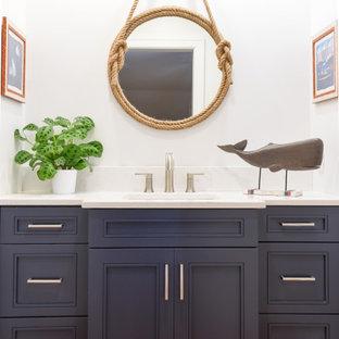 Immagine di una piccola stanza da bagno per bambini stile marino con ante lisce, ante blu, pareti bianche, lavabo sottopiano, top in superficie solida, pavimento marrone, top bianco, un lavabo e mobile bagno incassato