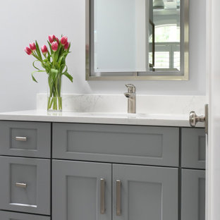 Example of a small beach style kids' ceramic tile, multicolored floor and single-sink toilet room design in Atlanta with flat-panel cabinets, gray cabinets, gray walls, an undermount sink, quartz countertops, yellow countertops and a built-in vanity
