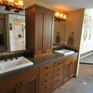Ispirazione per una stanza da bagno padronale american style di medie dimensioni con ante lisce, ante in legno bruno, vasca da incasso, piastrelle nere, piastrelle in ceramica, pareti gialle, pavimento con piastrelle in ceramica, lavabo da incasso e top in superficie solida