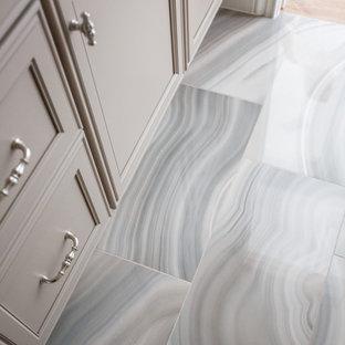 ジャクソンビルのビーチスタイルのおしゃれな浴室 (レイズドパネル扉のキャビネット、グレーのキャビネット、一体型トイレ、ベージュのタイル、磁器タイル、ベージュの壁、磁器タイルの床、アンダーカウンター洗面器、珪岩の洗面台、ターコイズの床、開き戸のシャワー) の写真