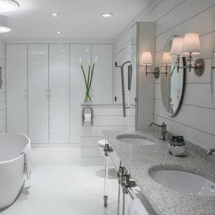 Diseño de cuarto de baño principal, campestre, de tamaño medio, con armarios con paneles lisos, puertas de armario blancas, bañera exenta, sanitario de pared, paredes blancas, suelo de cemento, lavabo bajoencimera, suelo blanco y encimera de terrazo