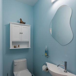 Imagen de cuarto de baño principal, clásico renovado, de tamaño medio, con armarios con paneles lisos, puertas de armario grises, bañera esquinera, ducha empotrada, sanitario de una pieza, baldosas y/o azulejos azules, baldosas y/o azulejos de vidrio, paredes blancas, suelo de baldosas de porcelana, lavabo encastrado, encimera de vidrio, suelo blanco y ducha con puerta con bisagras