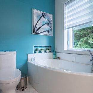 Imagen de cuarto de baño principal, tradicional renovado, de tamaño medio, con armarios con paneles lisos, puertas de armario grises, bañera esquinera, ducha empotrada, sanitario de una pieza, baldosas y/o azulejos azules, baldosas y/o azulejos de vidrio, paredes blancas, suelo de baldosas de porcelana, lavabo encastrado, encimera de vidrio, suelo blanco y ducha con puerta con bisagras