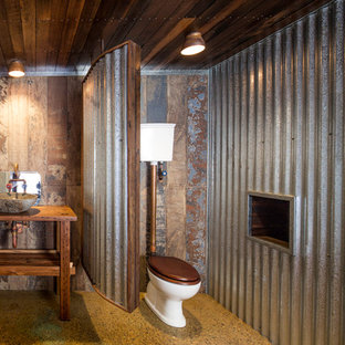 Photo of a mid-sized industrial bathroom in Brisbane with open cabinets, a two-piece toilet, concrete floors, a vessel sink and wood benchtops.