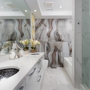Design ideas for a medium sized contemporary ensuite bathroom in Vancouver with flat-panel cabinets, an alcove shower, a one-piece toilet, stone slabs, white walls, marble flooring, a submerged sink, quartz worktops, white floors, a hinged door, white worktops, white cabinets and multi-coloured tiles.