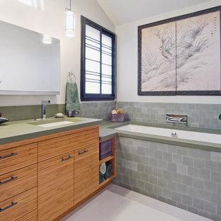Ejemplo de cuarto de baño actual con lavabo bajoencimera, armarios con paneles lisos, puertas de armario de madera oscura, bañera encastrada sin remate, baldosas y/o azulejos grises y encimeras verdes