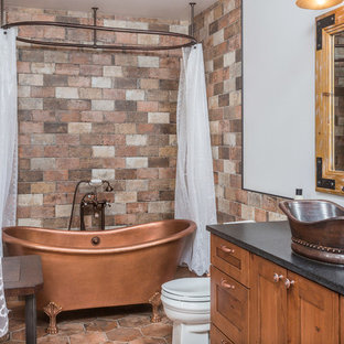 Example of a mid-sized mountain style 3/4 multicolored tile ceramic floor bathroom design in Other with shaker cabinets, medium tone wood cabinets, white walls, a vessel sink, a two-piece toilet and engineered quartz countertops