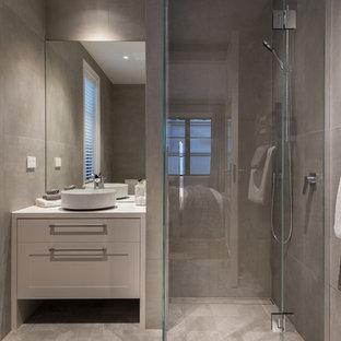 Ejemplo de cuarto de baño principal, grande, con puertas de armario beige, sanitario de una pieza, baldosas y/o azulejos grises, paredes grises, lavabo sobreencimera, suelo gris, armarios con paneles empotrados, ducha empotrada y encimera de azulejos