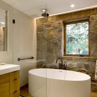 Rustik inredning av ett en-suite badrum, med släta luckor, skåp i ljust trä, ett fristående badkar, en dusch/badkar-kombination, beige väggar, ett integrerad handfat och med dusch som är öppen