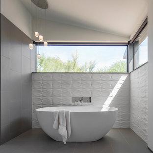 Foto di una stanza da bagno padronale minimal con vasca freestanding, piastrelle grigie, pareti multicolore e pavimento grigio